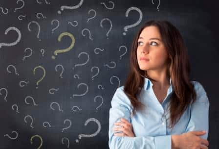 Young woman surrounded by question marks