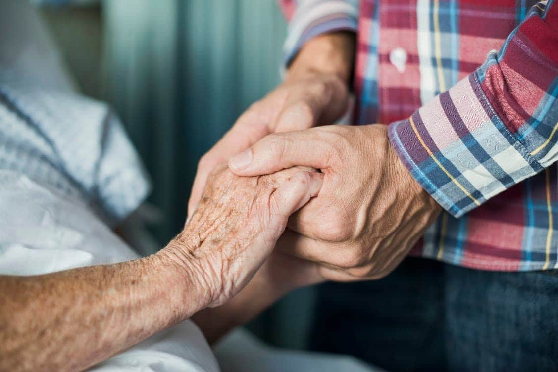 An elderly person holding hands with their caregiver.