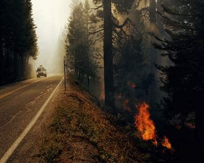 A van leaving an area with wildfires.